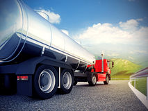 Röd lastbil på asfaltvägen under blå himmel Arkivfoto
