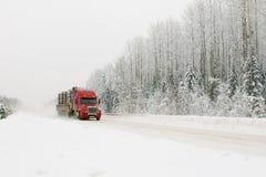 Röd lastbil på vintervägen Arkivbild