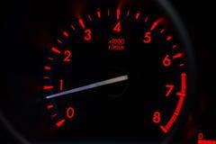 Röd ligjt på hastighetsmätaren i bil Arkivfoto