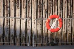 Röd livboj med repet på metallräcke Arkivfoton