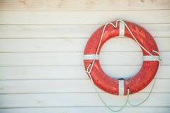 Röd livboj på en vit trävägg Bakgrund copyspace fotografering för bildbyråer