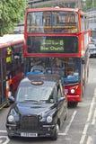 Röd London buss och svart taxi tillsammans i London royaltyfri bild