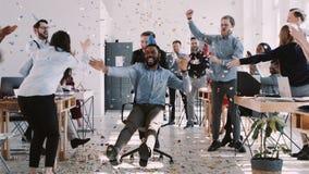 RÖD lycklig ung svart affärsman för EPIC-W som firar födelsedag på kontorsarbetsplatspartiet med konfettiultrarapid arkivfilmer