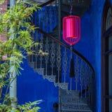 Röd lykta, blå vägg, bambu och en spiraltrappuppgång Arkivbilder