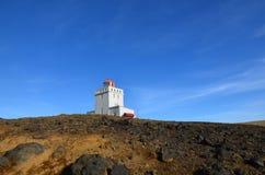 Röd lykta och vittornfyr i Vik Iceland arkivfoto