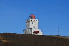 Röd lykta på en vit tornfyr i Vik Iceland Arkivbild