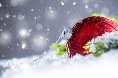 Röd lyxig boll för jul i snö och abstrakt snöig atmosfär arkivfoton