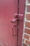 Röd målad hänglås på låst dörr Arkivfoton