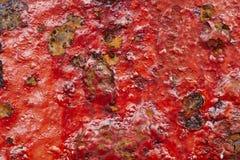 Röd målarfärg över en metallisk texturerad och rostig bakgrund Royaltyfri Fotografi