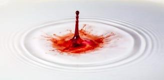 Röd målarfärgdroppe plaskar in i vatten Arkivfoton