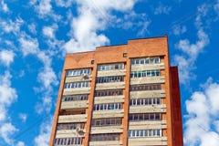 Röd mång--våning byggnad med trådar på bakgrunden av blått s Royaltyfria Foton