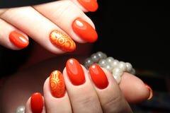 Röd manikyr med pärlor Arkivfoto