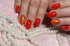Röd manikyr med pärlor Arkivbild