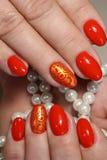 Röd manikyr med pärlor Royaltyfri Bild