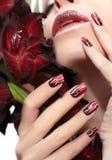 Röd manikyr med vita krabba linjer Royaltyfria Foton