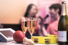 Röd maraca i karaokeklubba, med champagneflaskan och par av Arkivbilder