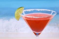 Röd Martini coctail med en limefrukt på stranden arkivbilder