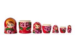 Röd Matreshka för rysk dockasouvenir ljus, purpurfärgad och grön blommamodell på den vit bakgrund isolerade closeupen royaltyfri fotografi