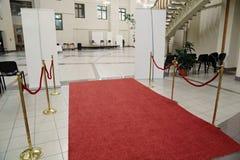 Röd matta och tom korridor arkivfoto
