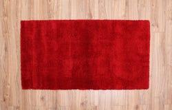 Röd matta på en parkett Arkivfoton
