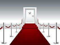 Röd matta som leder till dörren med silverstjärnan Arkivfoto
