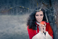 Röd med huva kvinna som rymmer den Apple sagaståenden Arkivfoton