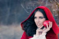 Röd med huva kvinna som rymmer den Apple sagaståenden Arkivbild