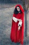 Röd med huva kvinnasagastående Royaltyfri Foto