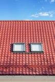 Röd metall belagt med tegel tak med nya vindskupefönster, tak Windows, takfönster och takskydd från snö BoardÑŽ Arkivfoton