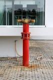 Röd metallisk brandpostanslutning på gatan Arkivbild