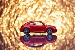 Röd metallmodellbil med utsmyckad skinande guld- bakgrund som är full av gnistor ut ur fokus Arkivfoto