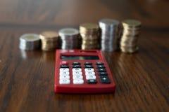 Röd miniräknare med buntar av mynt i bakgrunden arkivbilder