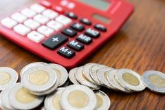 Röd miniräknare med mynt i förgrund Royaltyfria Foton