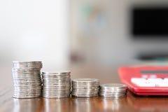 Röd miniräknare med mynt som visar grafen av förminskande kostnader Arkivfoton