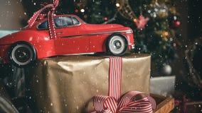 Röd modellbil och en julgåva som kombineras med fallande snö stock illustrationer