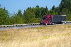 Röd modern halv lastbil- och svarttarpsläp Royaltyfri Bild