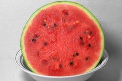 Röd mogen vattenmelon på ett stort uppläggningsfat arkivbilder