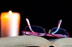 Röd monokel på den öppnade boken, stearinljusljus royaltyfria foton