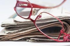 Röd monokel på en bunt av den vikta tidningen Royaltyfri Bild