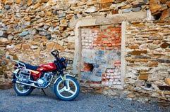 Röd moped som parkeras nära en stenvägg Fotografering för Bildbyråer