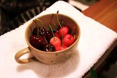 Röd ny körsbär i en kopp Arkivbilder