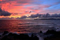 Röd och blå himmel över Alghero den steniga kusten Royaltyfria Foton