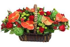 Röd-och-gräsplan blom- ordning i en vide- korg. Royaltyfria Foton