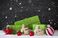 Röd och grön julgarnering, snö, svart cementvägg, snöflingor Royaltyfri Foto