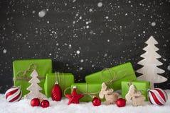 Röd och grön julgarnering, svart cementvägg, snö, snöflingor Royaltyfri Bild