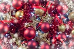Röd och guld- bakgrund för för julpyntleksakerbollar och stjärnor med en girland av ljus royaltyfria foton