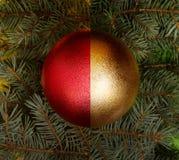 Röd och guld- boll och Christmass träd som bakgrund arkivbild