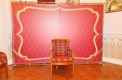Röd och guld improviserad studio i den barocka stilen framme av den klassiska festliga inre stol som sitter Royaltyfri Foto