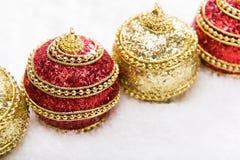 Röd och guld- jul klumpa ihop sig i snö, julbakgrund Royaltyfria Foton
