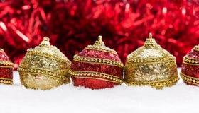 Röd och guld- jul klumpa ihop sig i snö med glitter och snöflingor, julbakgrund Royaltyfria Bilder